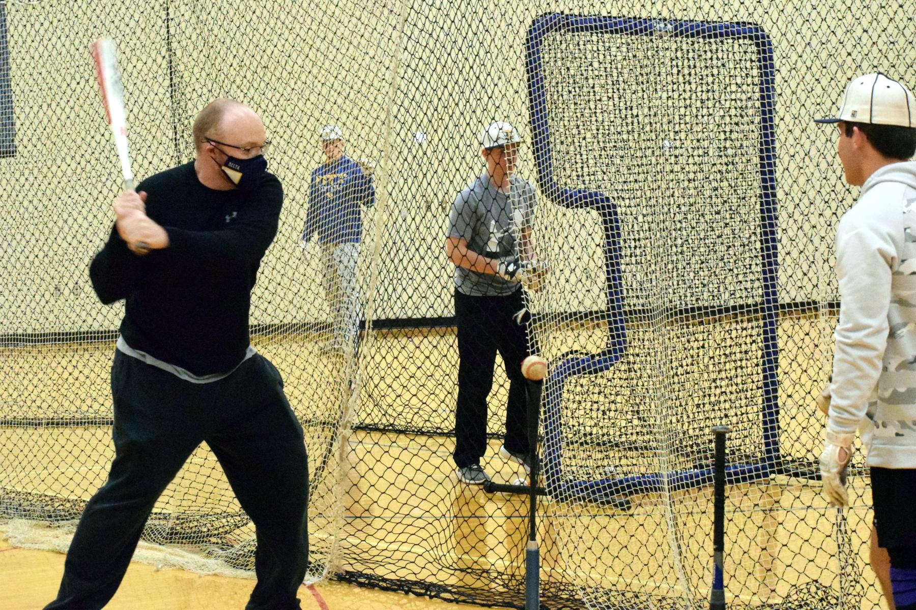 Coach swings bat